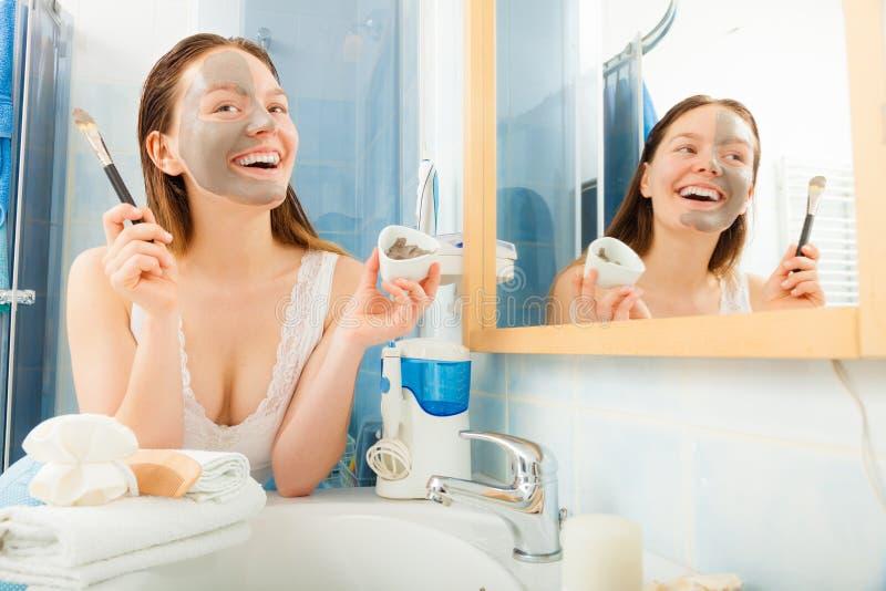 Vrouw die modder gezichtsmasker toepassen stock foto's
