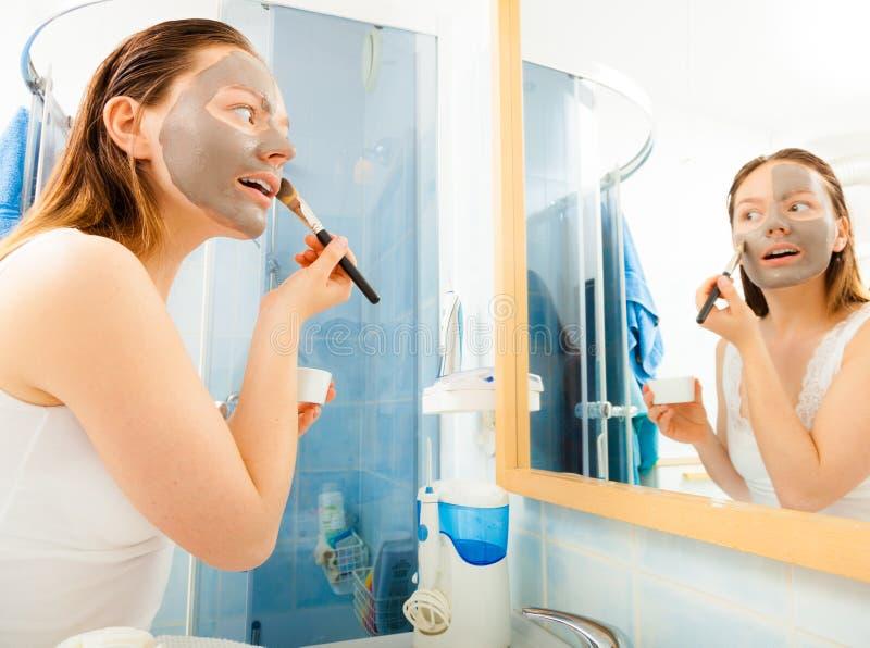 Vrouw die modder gezichtsmasker toepassen stock afbeelding