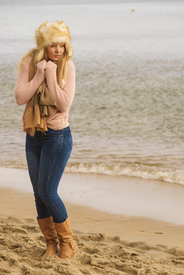 Vrouw die in modieuze uitrusting koud door het overzees voelen royalty-vrije stock foto