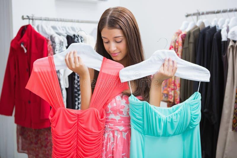 Vrouw die moeilijkheden hebben die kleding kiezen stock fotografie
