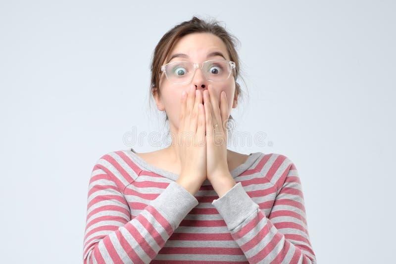 Vrouw die mond behandelen met hand en bij camera staren stock afbeeldingen