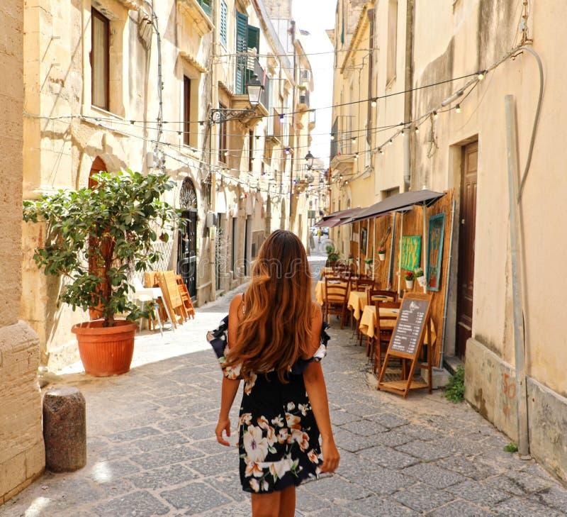 Vrouw die in mooie gebloeide kleding in straat van Syracuse, Sicilië lopen Achtermening van vrolijk en gelukkig meisje in het typ royalty-vrije stock fotografie
