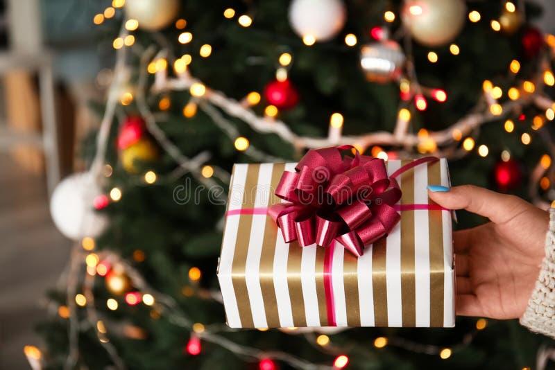 Vrouw die mooie gift houden dichtbij Kerstboom royalty-vrije stock foto