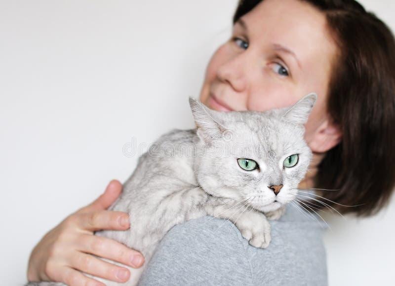 Vrouw die mooie grijze kat houdt royalty-vrije stock fotografie