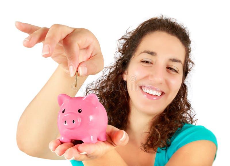Vrouw die muntstuk opnemen in spaarvarken stock fotografie