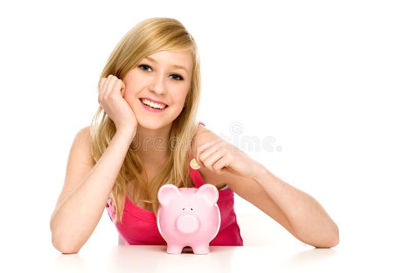 Vrouw die muntstuk in spaarvarken zet stock afbeeldingen