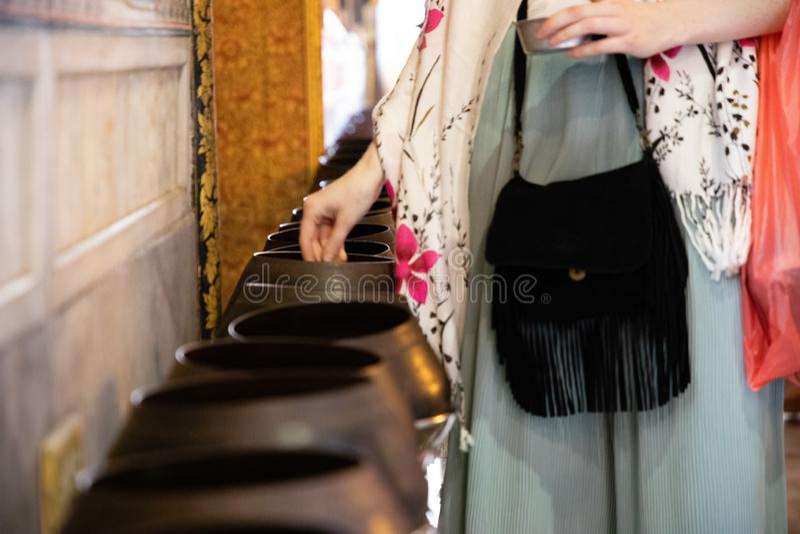 Vrouw die muntstukken in Thaise tempel voor geluk en welvaart schenken royalty-vrije stock foto