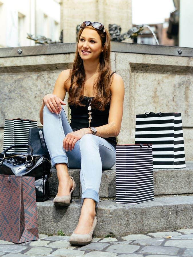 Vrouw die na het lange dag winkelen rusten stock foto