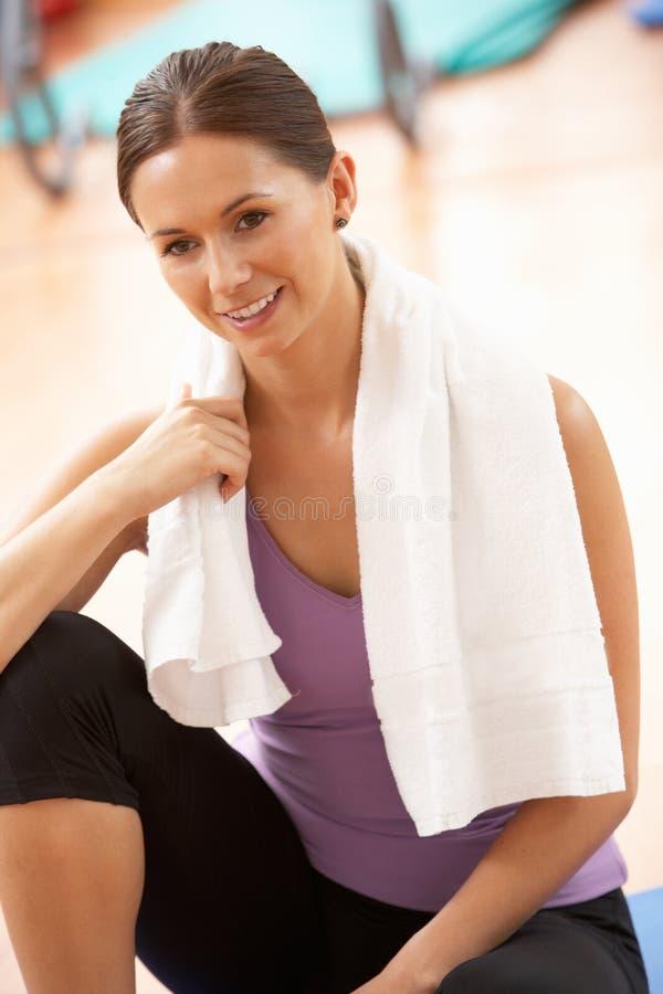 Vrouw die na Oefeningen in Gymnastiek rust stock foto's