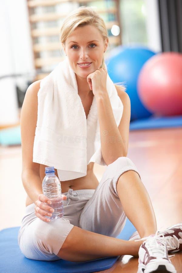 Vrouw die na Oefeningen rust stock fotografie