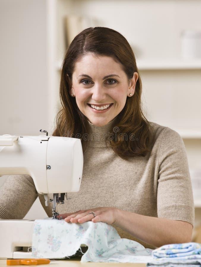 Vrouw die Naaimachine met behulp van stock foto's