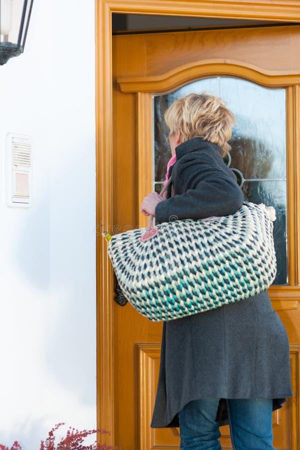 Vrouw die naar huis komt stock foto