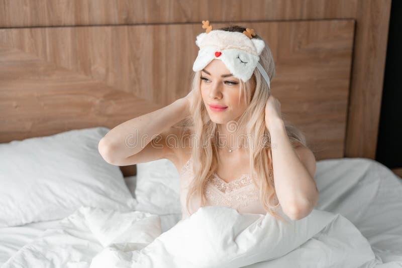 Vrouw die naar slaap voorbereidingen treffen te gaan en op een slaapmasker zetten Blinddoek op oog Ochtend in hotelruimte Wit hoo royalty-vrije stock afbeelding
