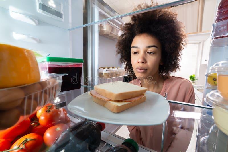 Vrouw die naar Voedsel in de Ijskast zoeken stock afbeeldingen