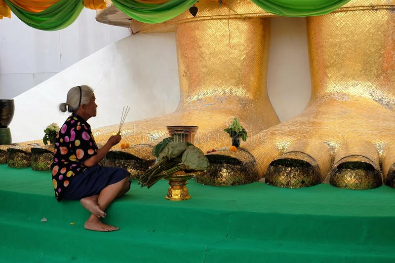 Vrouw die naast het Reuze Gouden Standbeeld van Boedha bidden royalty-vrije stock foto
