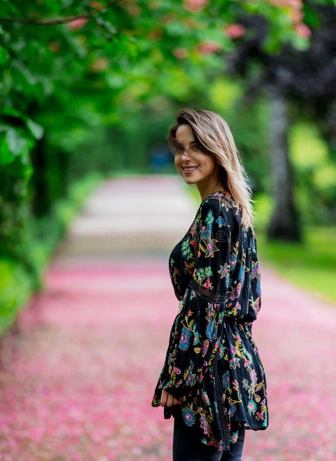 Vrouw die neer bij steeg met bloesembomen lopen stock afbeelding