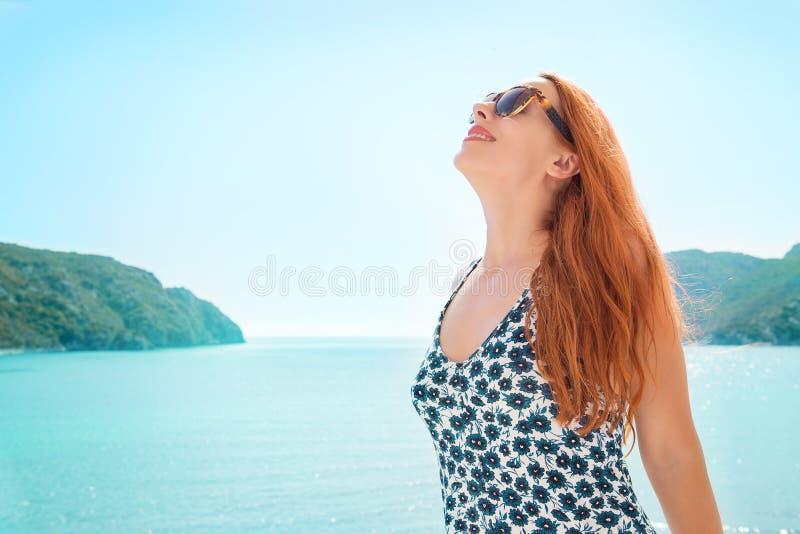 Vrouw die nemend diepe adem die van vrijheid en goed weer genieten door het overzees glimlachen Positieve menselijke emoties, gez stock foto