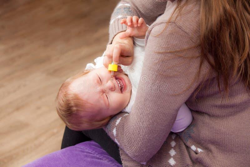 Vrouw die neusdalingen druipen aan een kind stock foto
