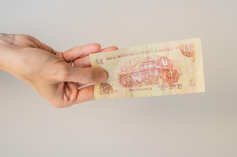 Vrouw die Ngultrum vijf bankbiljet Uit Bhutan in haar hand houden stock foto