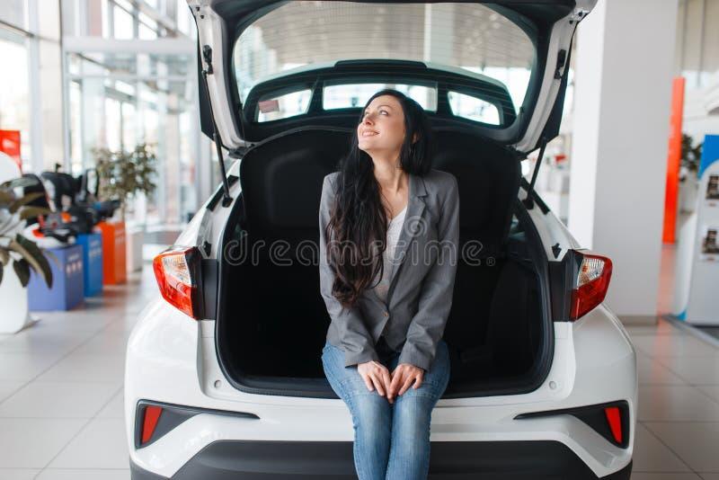 Vrouw die nieuwe auto, dame dichtbij de geopende boomstam kopen stock foto's