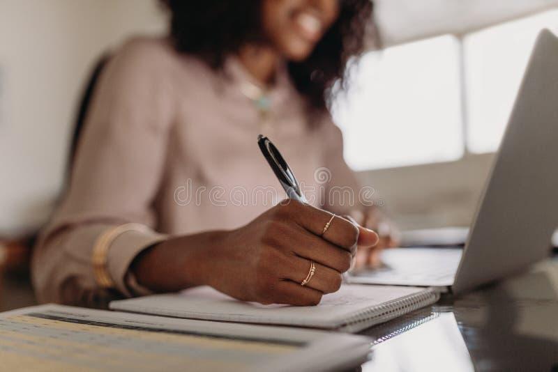 Vrouw die nota's maken bekijkend laptop die van huis werken stock afbeelding