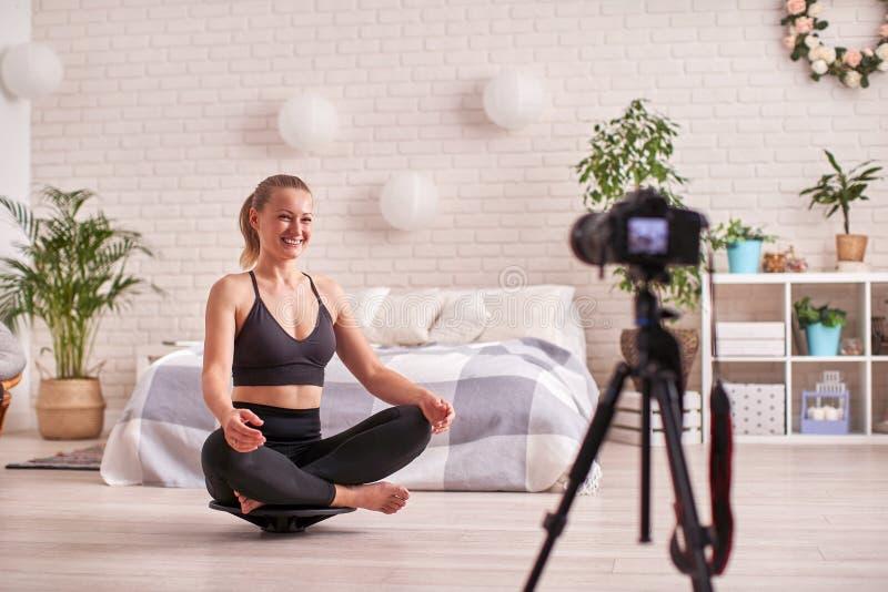 Vrouw die oefening op een speciale simulatorstabilisator doen het blonde de atletische sportkleding, huis uitoefende versterkt de royalty-vrije stock foto