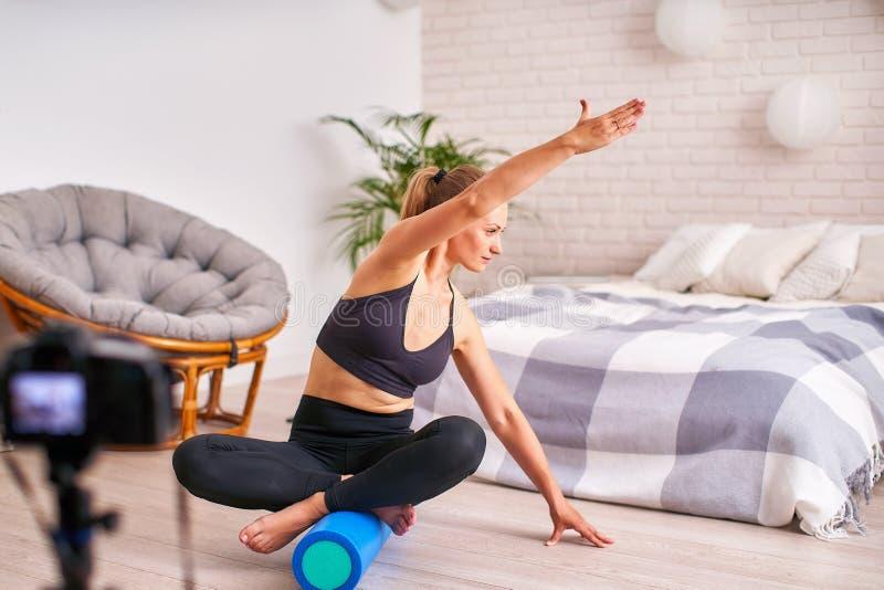 Vrouw die oefening op een speciale simulatorstabilisator doen het blonde de atletische sportkleding, huis uitoefende versterkt de stock foto's