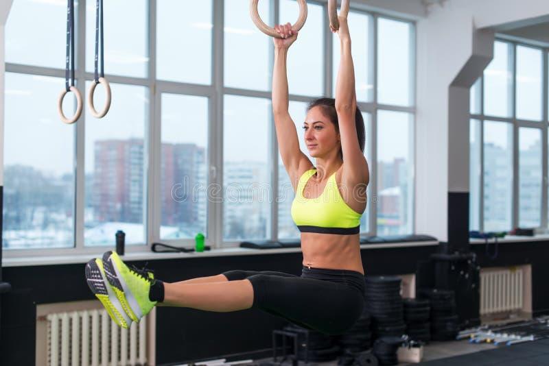 Vrouw die oefeningen met ringen, het hangen doen, die benen opheffen, ABS opleiding royalty-vrije stock foto
