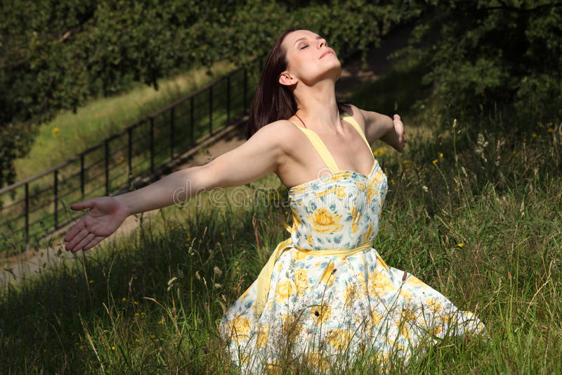 Vrouw die omhoog de zomerzon in platteland doorweekt royalty-vrije stock foto