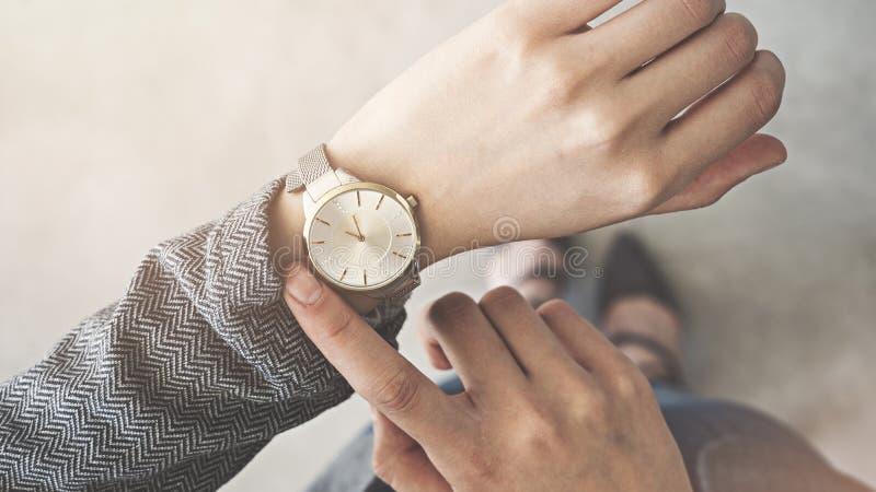 Vrouw die omhoog haar horlogetribune kijken stock afbeeldingen
