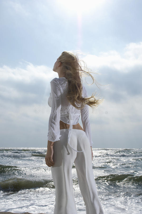 Vrouw die omhoog Hemel tegen Oceaan bekijken royalty-vrije stock fotografie