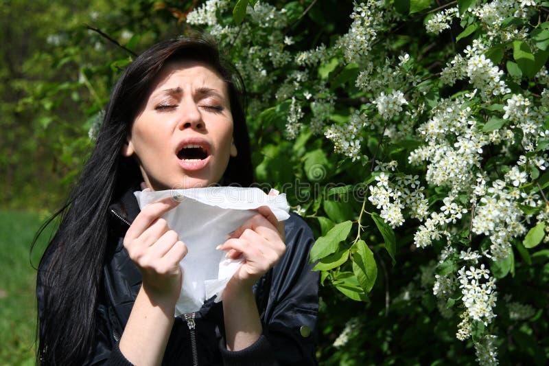 Vrouw die onder bloemen niest royalty-vrije stock afbeelding