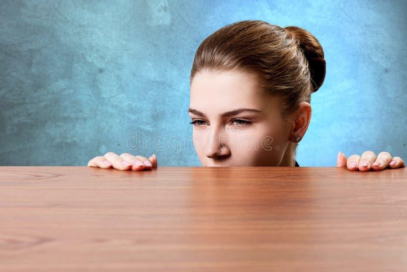 Vrouw die onder de rand van houten lijst piepen stock fotografie
