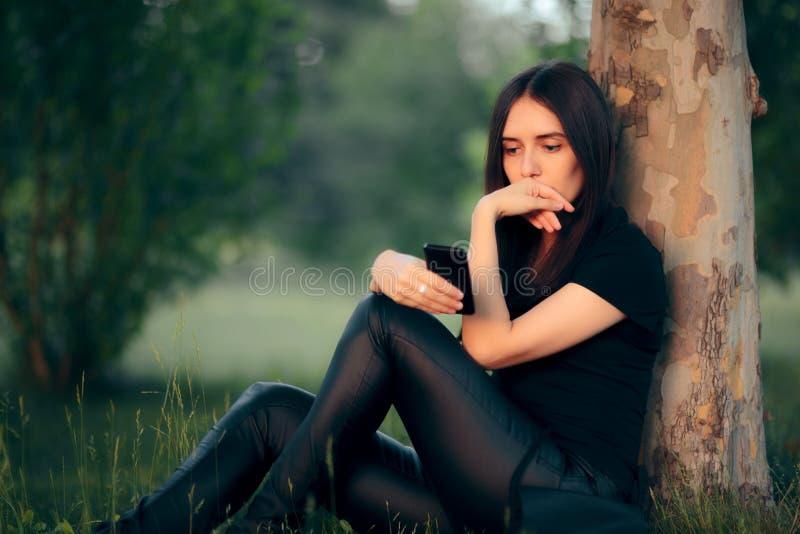 Vrouw die onder een Boom rusten die Haar Smartphone controleren royalty-vrije stock afbeelding
