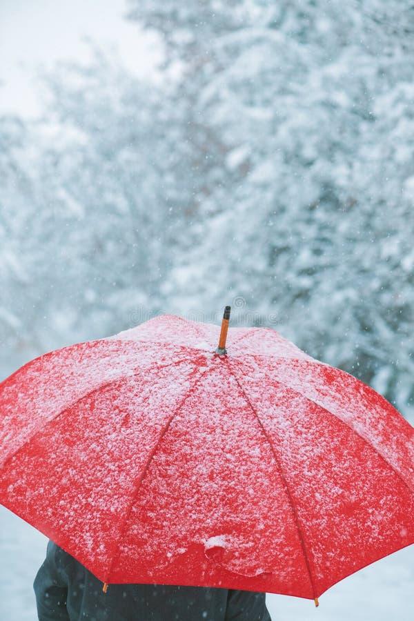 Vrouw die onder rode paraplu in de wintersneeuw lopen stock fotografie