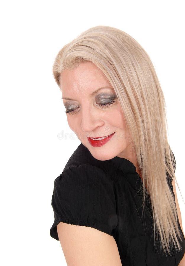 Vrouw die onderaan het glimlachen van met haar kijken lang blond haar royalty-vrije stock foto