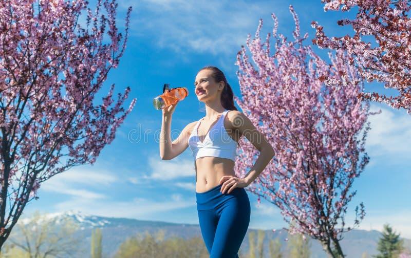 Vrouw die onderbreking van het runnen van drinkwater hebben royalty-vrije stock afbeelding