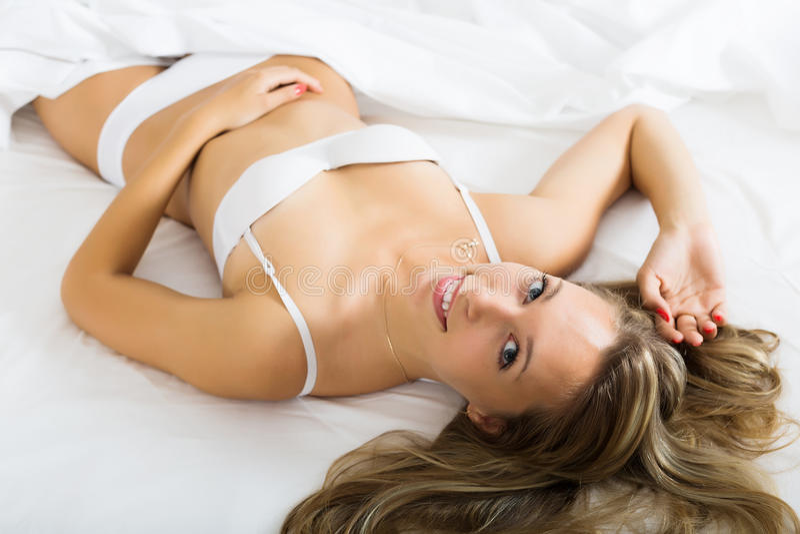 Vrouw die in ondergoed op bed leggen royalty-vrije stock afbeelding