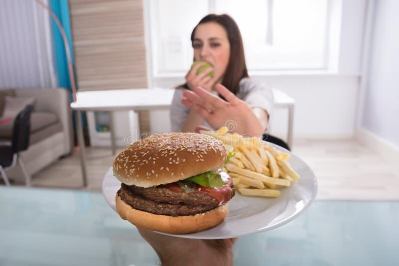 Vrouw die Ongezond Voedsel weigeren terwijl het Eten van Fruit stock foto