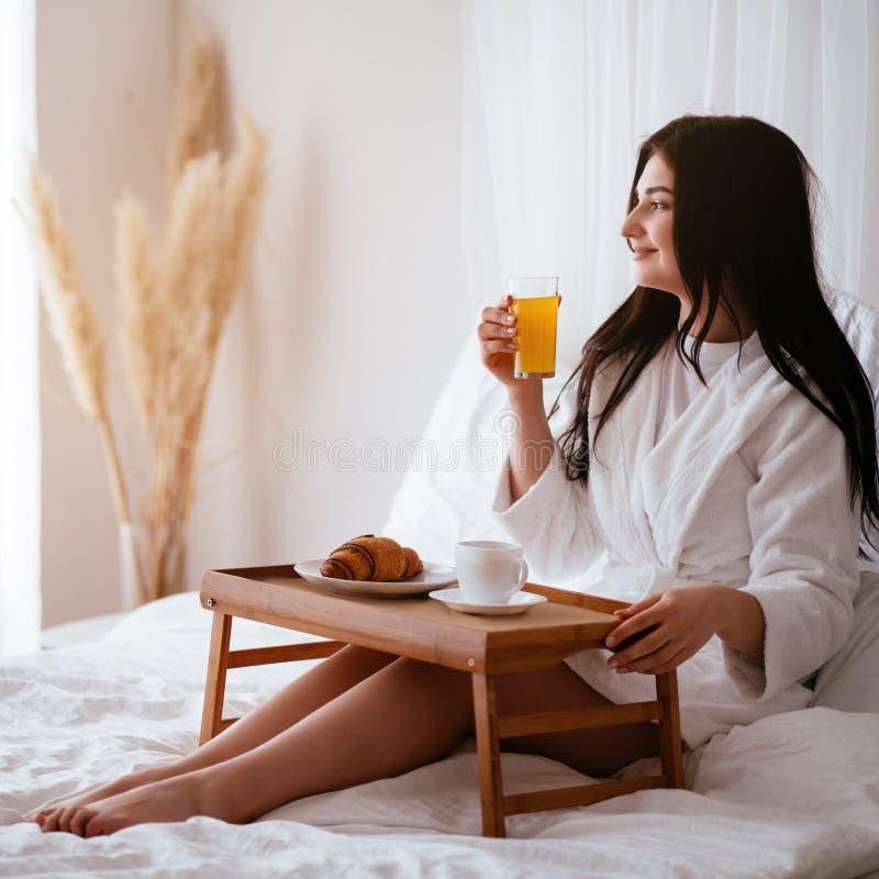 Vrouw die ontbijt in bed in comfortabele hotelruimte hebben stock afbeelding