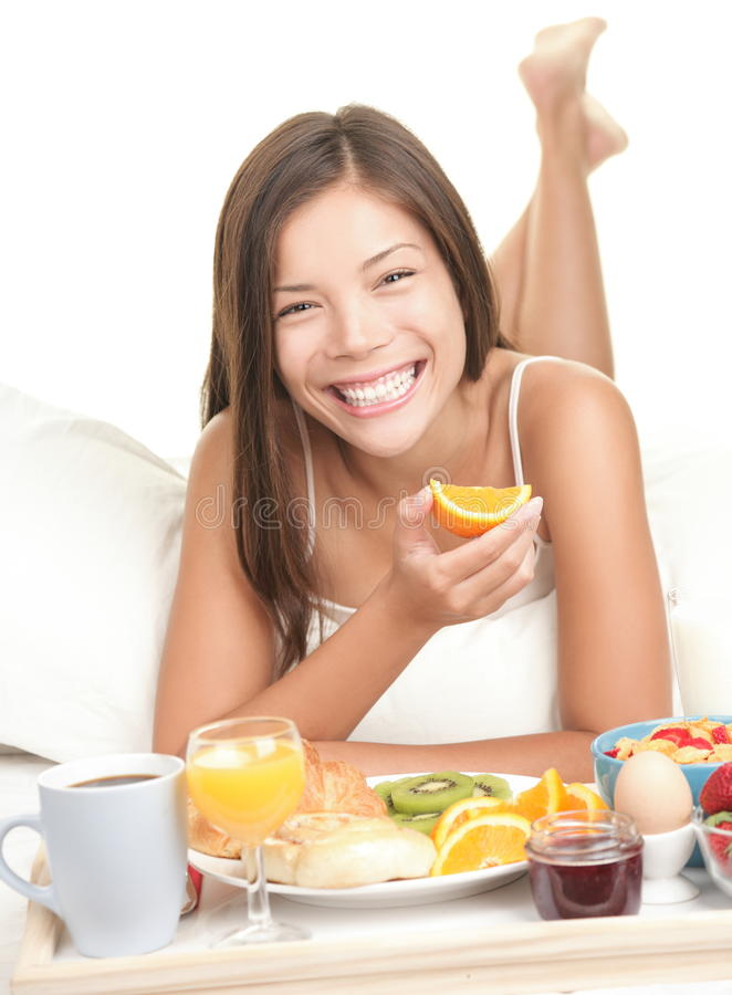 Vrouw die ontbijt in bed eet royalty-vrije stock afbeelding