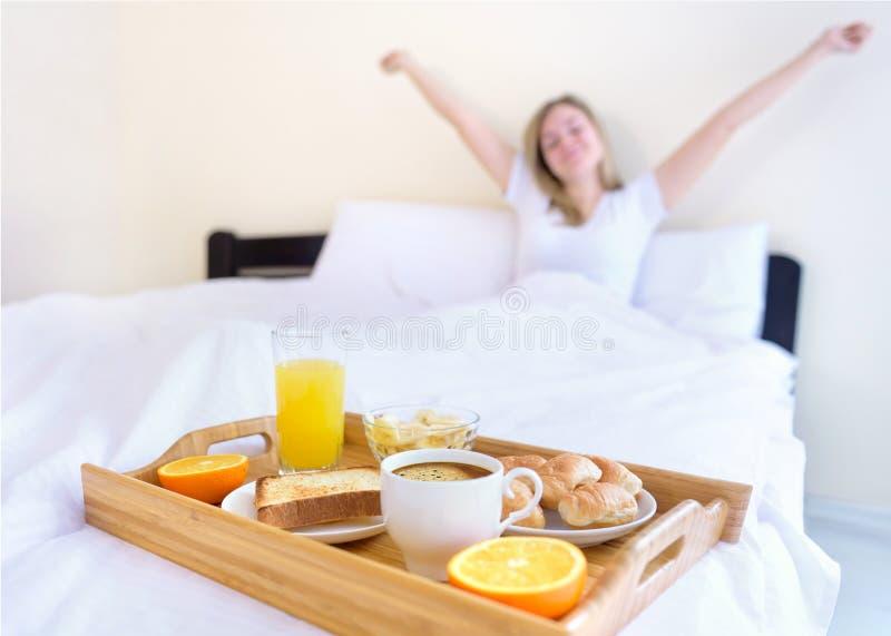 Vrouw die ontbijt in bed eet stock afbeeldingen