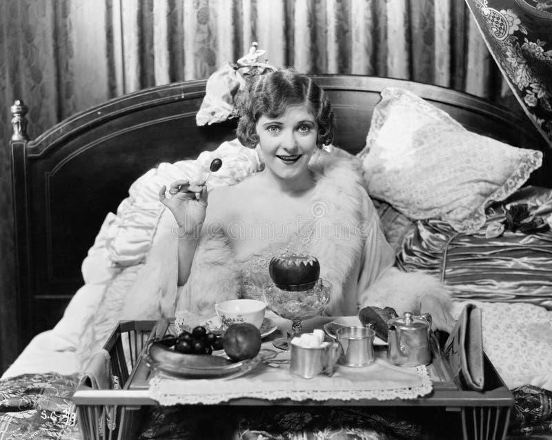 Vrouw die ontbijt in bed eten (Alle afgeschilderde personen leven niet langer en geen landgoed bestaat Leveranciersgaranties die  royalty-vrije stock afbeeldingen