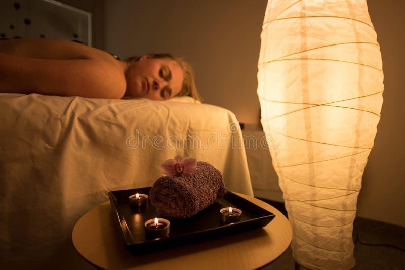 Vrouw die ontspannend achtermassage in cosmetic spa centrum in s genieten van stock fotografie