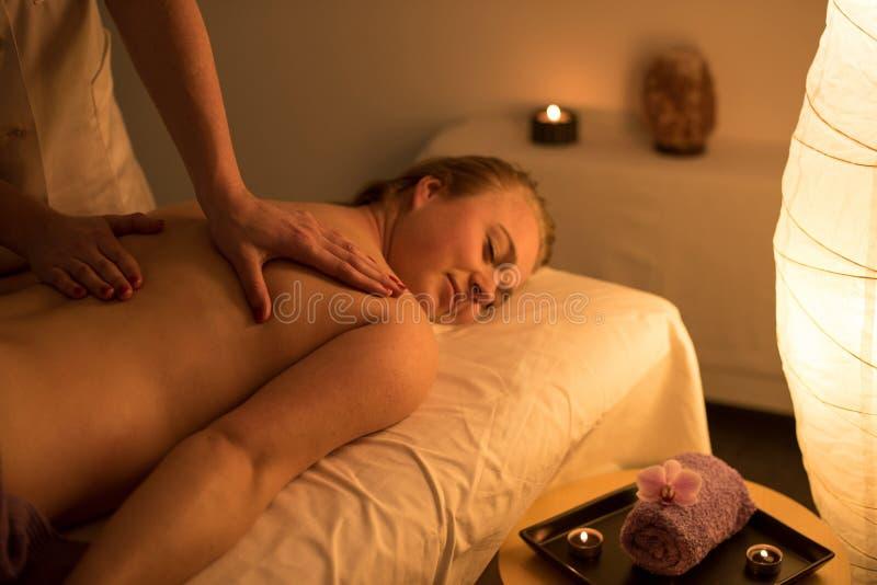 Vrouw die ontspannend achtermassage in cosmetic spa centrum in s genieten van royalty-vrije stock afbeelding