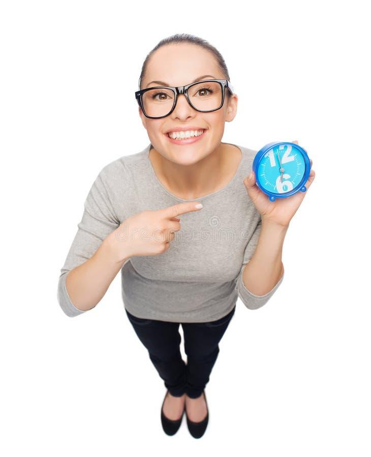 Vrouw die in oogglazen vinger richten aan blauwe klok stock foto