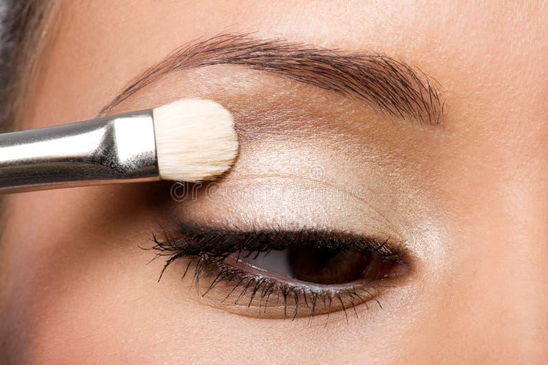 Vrouw die oogschaduw op ooglid toepast royalty-vrije stock afbeeldingen