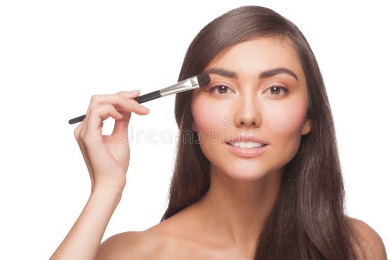 Vrouw die oogschaduw toepassen stock foto