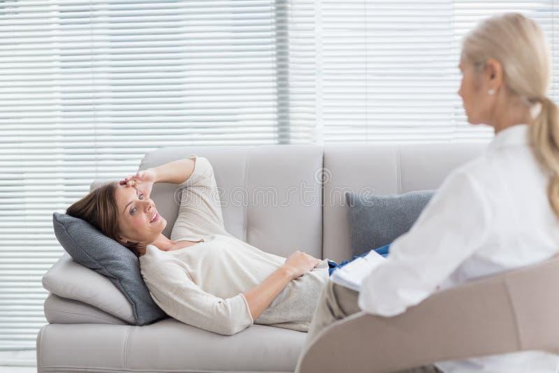 Vrouw die op bank liggen die aan therapeut spreken stock fotografie
