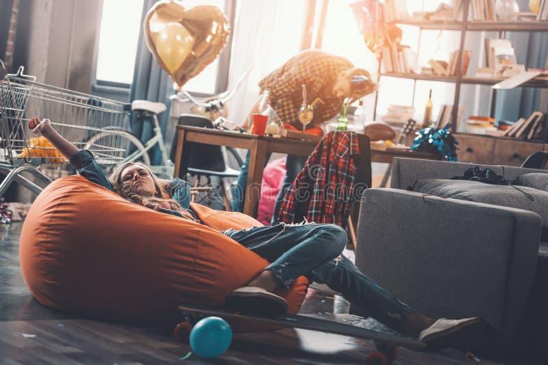 Vrouw die op beanbagstoel rusten terwijl man het schoonmaken erachter in slordige ruimte na partij stock fotografie